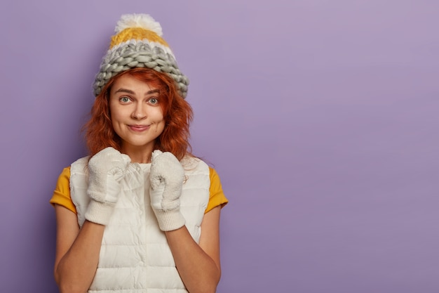 Bella giovane donna alza i pugni chiusi, indossa gilet, maglietta, guanti bianchi, copricapo sulla testa, guarda con sguardo intrigante alla telecamera, isolato sul muro viola