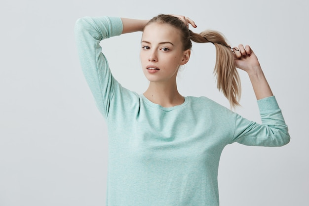 Good-looking young female with charming dark eyes and blonde hair in pony tail wearing light blue sweater