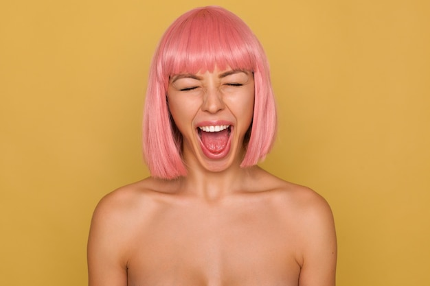 Good looking young female with short pink hair keeping her mouth wide opened while screaming loud with closed eyes, isolated over mustard wall