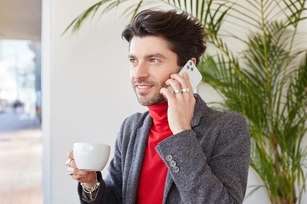 Bello giovane maschio bruna non rasato felice tenendo la tazza di caffè in mano alzata e sorridendo piacevolmente, effettuando la chiamata mentre posa sopra l'interno del caffè