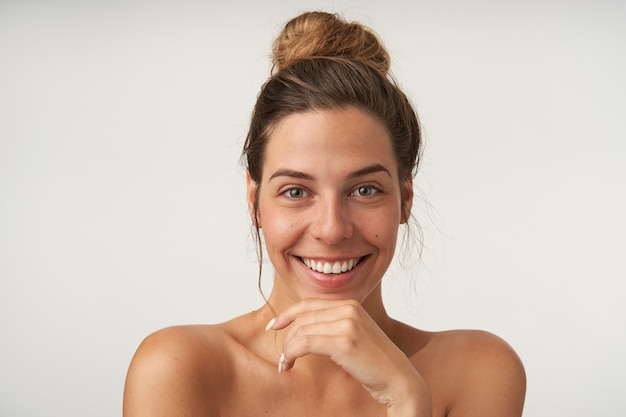 Good looking young happy female posing on white with charming smile, wearing bun hairstyle and no make-up, keeping hand on her chin