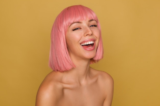 Good looking young happy pretty lady with short pink hair throwing back her head while laughing cheerfully, being in nice mood while posing over mustard background
