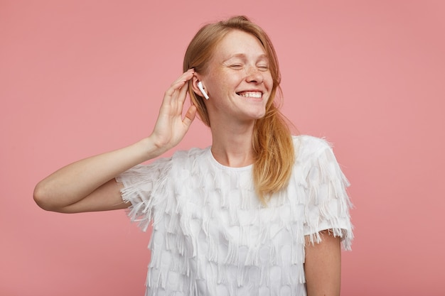 Good looking young happy redhead woman with natural makeup raising hand to her head while posing over pink background, keeping eyes closed while enjoying music track in her earphones