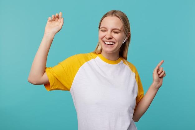 Хорошо выглядящая молодая радостная блондинка с длинными волосами слушает музыку в наушниках и счастливо улыбается с закрытыми глазами, танцует с поднятыми руками, позирует на синем