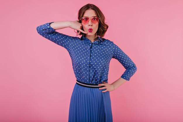 青い服装でポーズをとる波状の髪型の格好良い若い女性。ピンクの壁の近くに立っている眼鏡のエレガントなヨーロッパの女性。