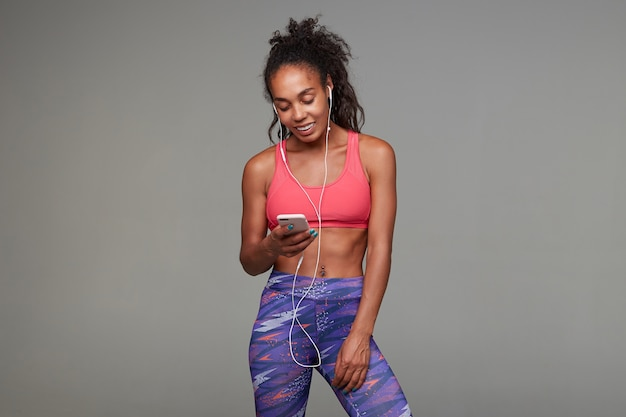 Good looking young lovely dark skinned curly brunette sportswoman with belly button piercing holding smartphone in raised hand and smiling happily, isolated