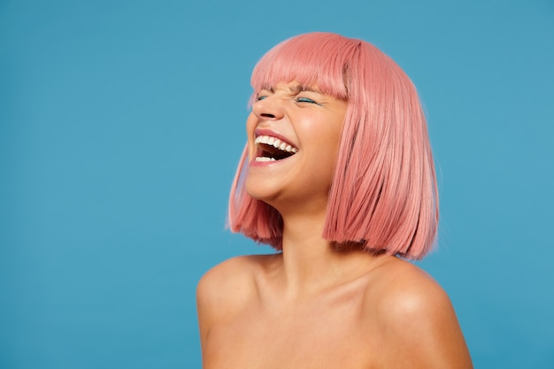 파란색 배경 위에 포즈를 취하는 동안 축제 메이크업을 입고 닫힌 눈으로 즐겁게 웃으면 서 밥 이발이 그녀의 머리를 뒤로 던지는 좋은 찾고 젊은 사랑스러운 분홍색 머리 아가씨