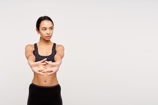 Good looking young lovely sporty dark haired woman without makeup making exercises for her hands while standing over white wall in sporty clothes