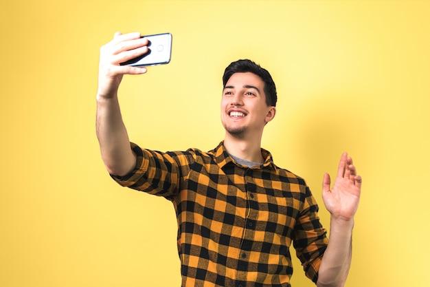 Красивый молодой человек в непринужденной желтой рубашке, видеочат с помощью смартфона на желтом фоне