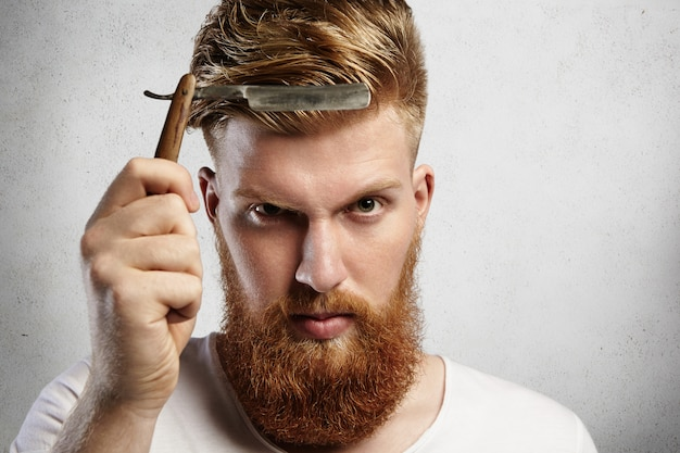 Good-looking young man with red beard holding barbershop accessory. caucasian barber demonstrating sharp blade of his old-fashioned straight razor, determined to shave clients.