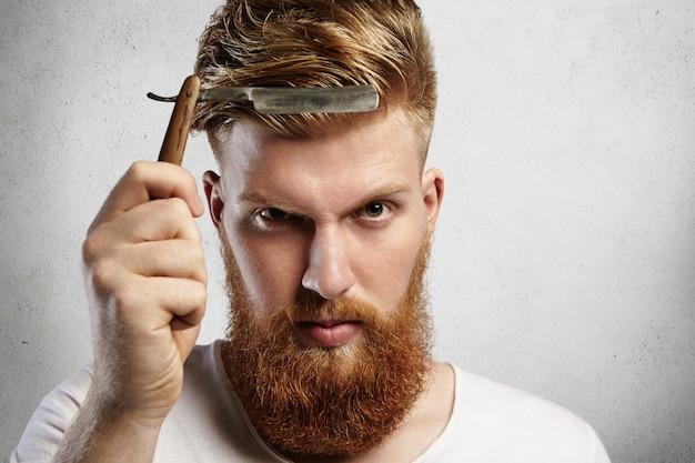 理髪店のアクセサリーを保持している赤ひげのかっこいい若い男。白人の理髪師が、昔ながらのまっすぐなかみそりの鋭い刃を示し、クライアントを剃ることを決意しました。