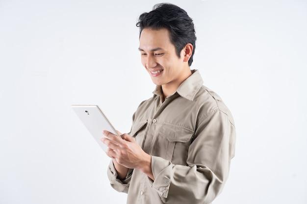 Красивый молодой механик в спецодежде, использующий планшетный компьютер для работы и улыбающийся