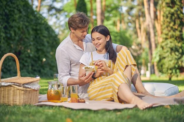 녹색 공원에서 시간을 보내는 흰색과 노란색 옷을 입은 잘 생긴 젊은이