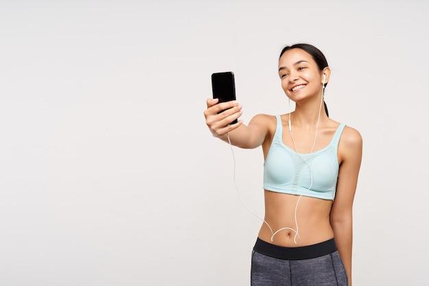 格好良い若い喜んで茶色の髪の女性が携帯電話で手を上げて自分のショットを撮り、白い壁の上に立って喜んで笑っている
