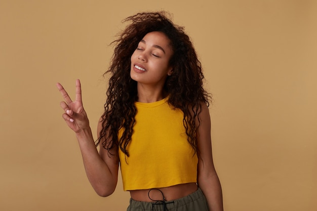 Good looking young pleased curly brunette lady with casual hairstyle keeping her eyes closed while showing victore sign, standing on beige