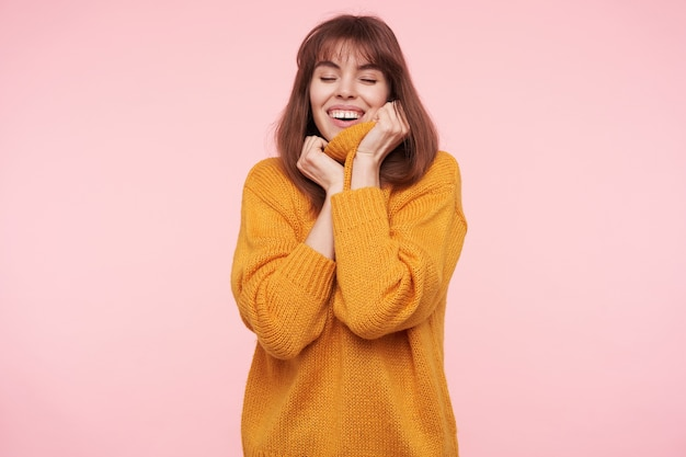 Good looking young positive brunette female keeping hands on her mustard knitted sweater and smiling cheerfully with closed eyes, isolated over pink wall