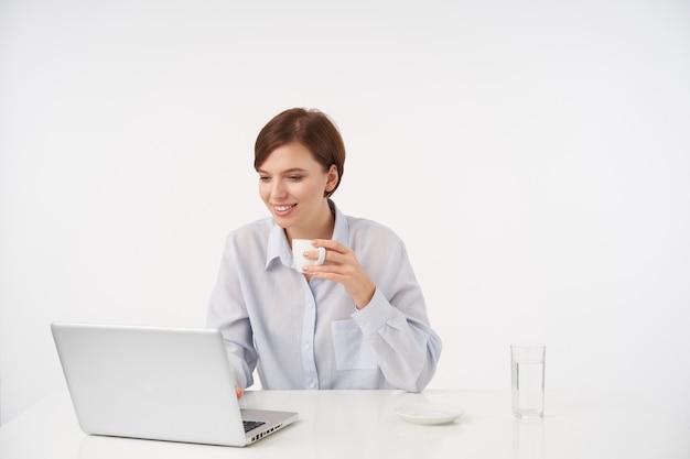 Красивая молодая позитивная брюнетка с короткими волосами и естественным макияжем, пьющая чашку кофе во время работы в офисе со своим ноутбуком, изолированная на белом