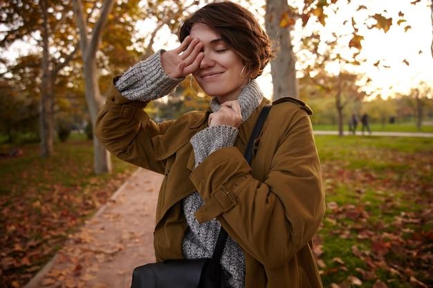 Bella giovane donna bruna dai capelli corti positiva, alzando la mano al viso e sorridendo piacevolmente con gli occhi chiusi, mentre in piedi sul parco sfocato