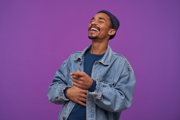 Good looking young pretty bearded brunette man with dark skin keeping palm on his body while laughing happily with closed eyes, standing against purple wall