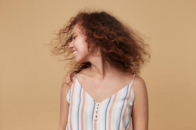 Хорошо выглядящая молодая симпатичная шатенка кудрявая дама в летнем топе машет головой и позитивно улыбается, стоя на бежевом с опущенными руками