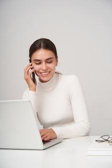 Bella giovane donna graziosa del brunette vestita in abiti formali tenendo il cellulare in mano alzata pur avendo una piacevole conversazione telefonica, in posa sopra il muro bianco