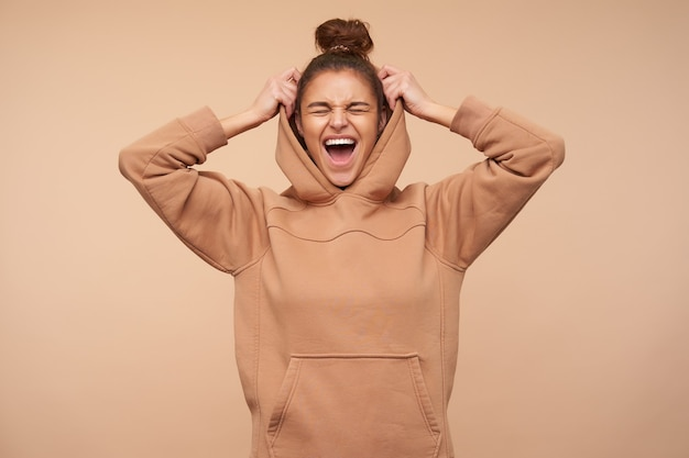Good looking young pretty brunette woman keeping her eyes closed while laughing happily, raising hand to her hood while standing against beige wall