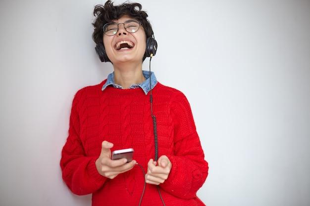 携帯電話で白い背景の上に立っている間ヘッドフォンを身に着けて、楽しく笑いながら彼女の頭を投げ返す眼鏡の格好良い若いかなり巻き毛のブルネットの女性