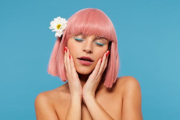 Bella giovane donna dai capelli rosa romantica con trucco festivo che tocca delicatamente il suo viso con le mani alzate e tiene gli occhi chiusi mentre è in piedi