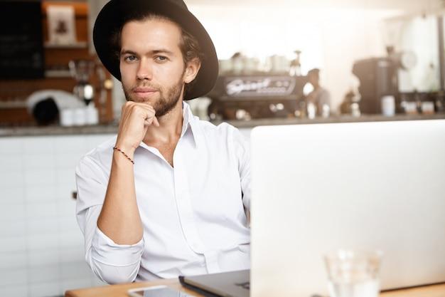 Красивый молодой самозанятый мужчина с бородой сидит в кафе перед современным ноутбуком, опираясь локтем на стол и серьезно сосредоточенный взгляд, работая онлайн на портативном компьютере
