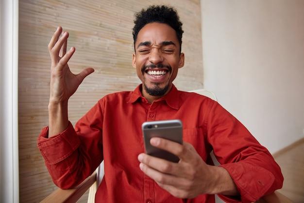 Симпатичный молодой бородатый парень с короткими волосами и темной кожей, держа глаза закрытыми, счастливо смеясь и держа мобильный телефон в поднятой руке, изолирован на бежевом интерьере