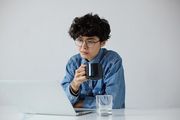 Симпатичная молодая коротковолосая кудрявая брюнетка с естественным макияжем держит чашку чая в поднятой руке и читает интересную статью на своем ноутбуке, изолированном