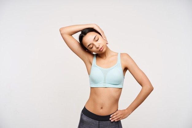 Good looking young slim brown haired lady keeping her eyes closed while making exercises forr neck and pulling head with raised hand, isolated over white wall