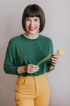 집에서 주말에 오싹한 녹색 스웨터에 잘 생긴 젊은 여자. 노란색 꽃과 함께 웃는 검은 머리 소녀의 실내 사진.