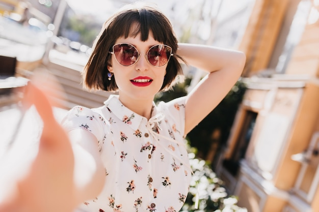 흐림 거리에 셀카를 만드는 선글라스에 잘 생긴 젊은 여자. 도시에서 시간을 보내는 유행 블라우스에 짧은 머리 귀여운 소녀.