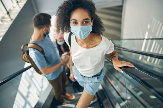 국제 공항의 움직이는 계단에 서있는 동안 사진 카메라를보고 흰 셔츠에 좋은 찾고 젊은 여자