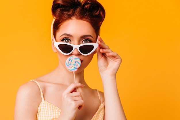 Good-looking young woman licking hard candy. front view of ginger pinup girl in sunglasses.