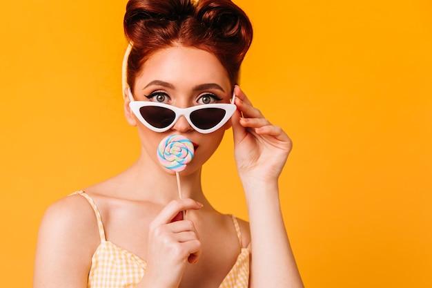 ハードキャンディーをなめるかっこいい若い女性。サングラスの生姜ピンナップガールの正面図。