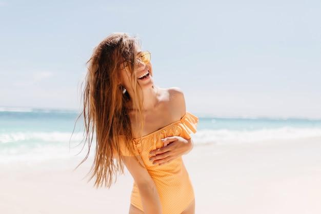 ビーチで真摯に笑いながらポーズをとる格好良い若い女性。澄んだ青い空の下で海の近くに立っているオレンジ色の水着の恍惚としたブルネットの少女。