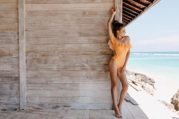 かっこいい若い女性は、木製の壁の近くでポーズをとってレトロな黄色の水着を着ています。海の近くで週末の朝を過ごす美しい日焼けした女の子の屋外の全身像。
