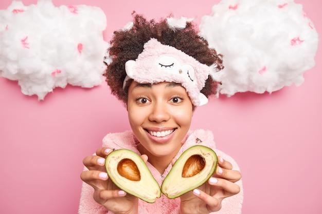 곱슬 머리를 가진 잘 생긴 젊은 여성은 피부를 돌보는 천연 화장품을 만들려고 아보카도의 절반을 보유하고 분홍색 벽에 수면 마스크를 착용하고 머리카락에 깃털이 있습니다.