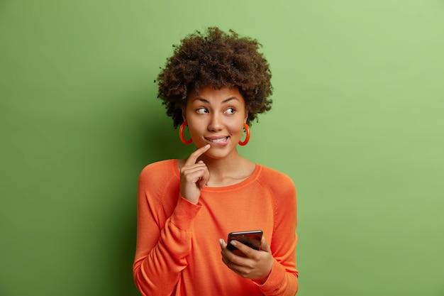 Bella giovane donna con i capelli ricci detiene lo smartphone moderno utilizza la nuova applicazione vestita in maglione arancione casual isolato sopra il muro verde pensa a qualcosa di piacevole