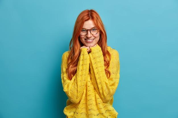 自然な生姜髪の格好良い若い女性は、あごの下に手を保ち、満足そうな笑顔で優しく光学メガネの黄色いニットセーターを着ています。