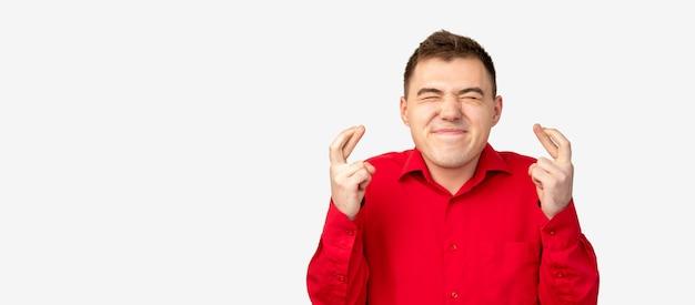 Жест удачи. удача удачи. возбужденный мужчина в красной рубашке со скрещенными пальцами, изолированными на белом копировальном пространстве. Premium Фотографии