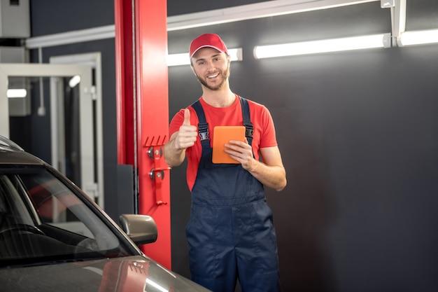 頑張って、仕事。ワークショップで車の近くに立っているokジェスチャーを示すタブレットで作業オーバーオールとキャップでうれしそうな若いひげを生やした男