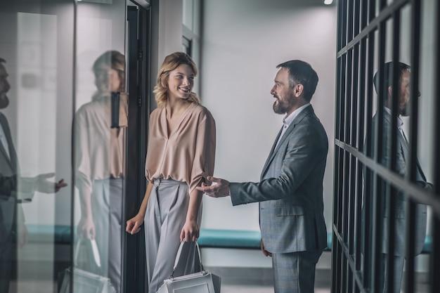좋은 매너. 건물의 복도에 서있는 사무실에 젊은 예쁜 여자 동료를 초대하는 비즈니스 성인 상냥한 남자 제스처