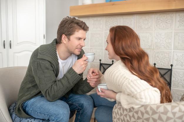 良い瞬間。自宅の暖炉のそばで一緒に余暇を過ごすコーヒーを飲む長髪の女性の手を握って思いやりのある男