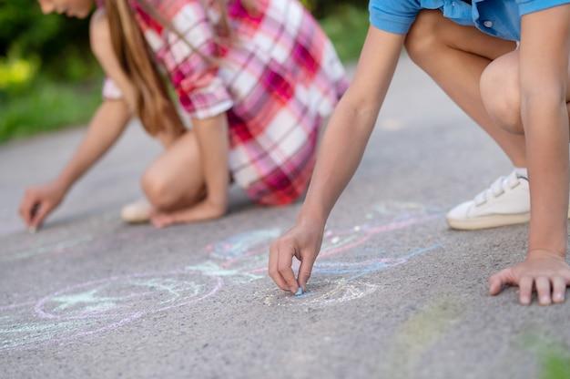 좋은 순간들. 아이들의 손은 따뜻한 날 공원의 아스팔트에 다양한 색의 크레용으로 그림을 그리고 있으며 얼굴은 보이지 않습니다