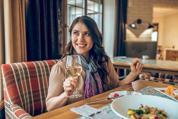 좋은 순간들. 검은 머리의 예쁜 여자가 식당의 테이블에 앉아 만족스러운 표정을 짓고 있다