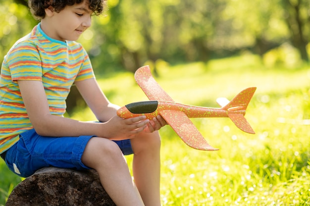 Good moments. happy boy with dark curly hair looking at toy plane while sitting on tree stump in nature on fine day