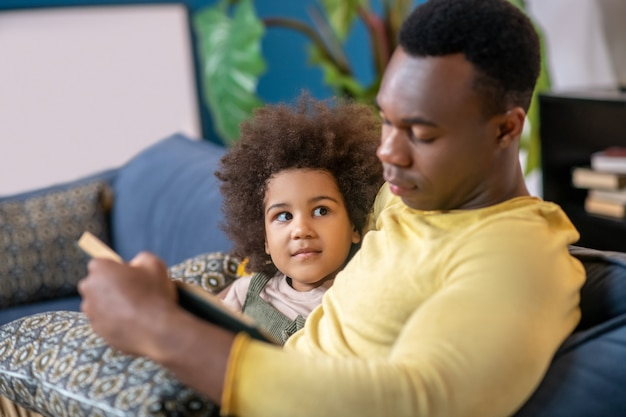 Good moments. little cute darkskinned girl looking lovingly at her dad reading book sitting next to him on sofa